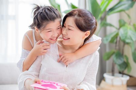 Fijne moederdag - dochter geeft thuis een kaart en cadeau aan haar moeder Stockfoto