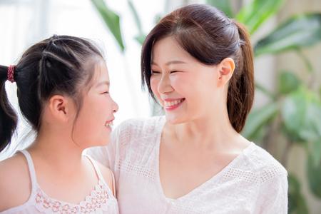 Mamá e hija se miran juntas y sonríen tiernamente