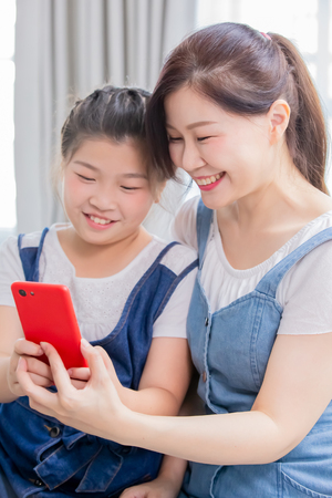 Daughter and mother use smart phone happily at home