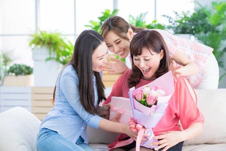 due figlie fanno regali a sua madre e celebrano la felice festa della mamma a casa