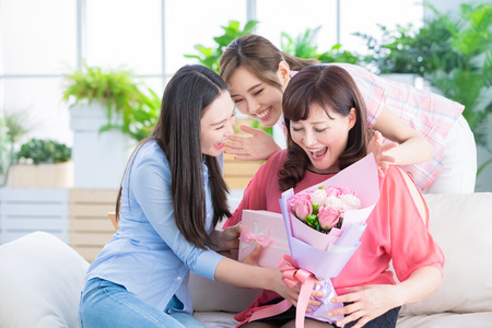 two daughters give gifts to her mom and celebrate happy mother day at home Фото со стока