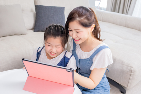 Mom and daughter use tablet happily at home Stockfoto