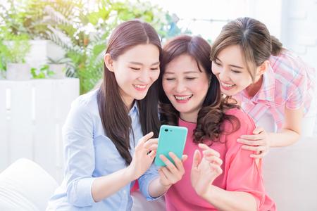 Les filles et la mère utilisent joyeusement le téléphone intelligent à la maison