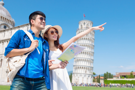 이탈리아 피사의 사탑을 방문할 때 커플이 세계 지도를 가져갑니다.