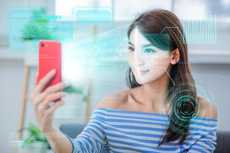 concepto de reconocimiento facial: chica asiática usa acceso biométrico por teléfono inteligente Foto de archivo
