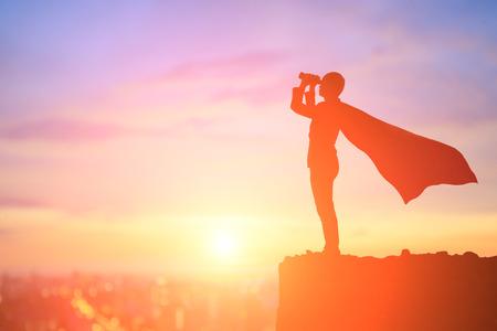 Silhouette des Supergeschäftsmannes nehmen Monokular auf dem Berg im Sonnenuntergang Standard-Bild