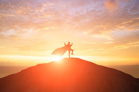 Silhouette eines Supergeschäftsmannes mit Umhang, der sich im Sonnenuntergang auf dem Berg aufgeregt fühlt