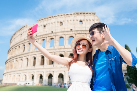 couple selfie happily with Colosseum in Italy Imagens