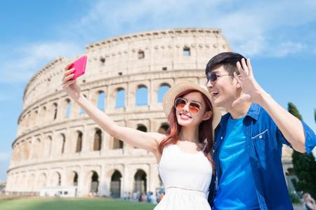 Pareja selfie felizmente con el Coliseo en Italia Foto de archivo
