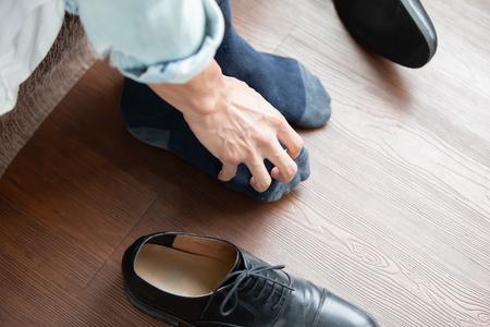 l'uomo d'affari gratta il prurito a mano con il problema del piede d'atleta