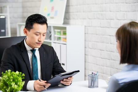 Le patron masculin asiatique interviewe une femme au bureau Banque d'images