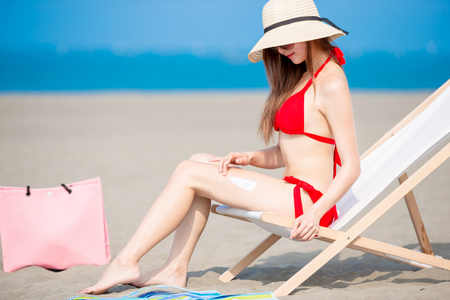 Summer sunblock concept - beauty asian woman apply the sunscreen lotion