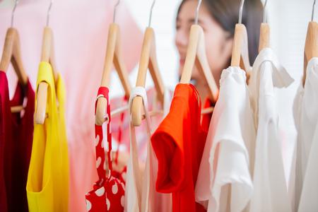 jonge vrouw die kleding kiest op een rek thuis of in de winkel