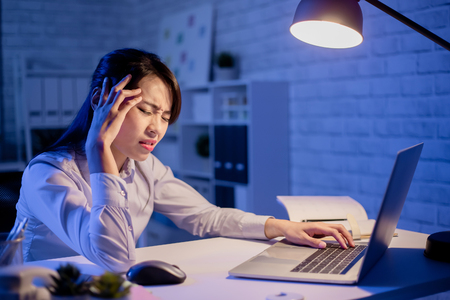 asian woman overtime work and had headache pain in the office Stock Photo