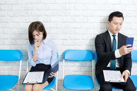 Male applicant is well prepared for interview by smart phone while female appplicant anxious about interview