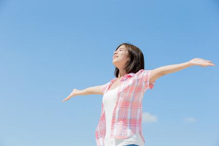 Aziatisch meisje voelt zich gelukkig en geniet van de natuur met een hemelachtergrond