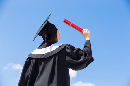 Aziatische afgestudeerde student voel je vrij met hemelachtergrond Stockfoto