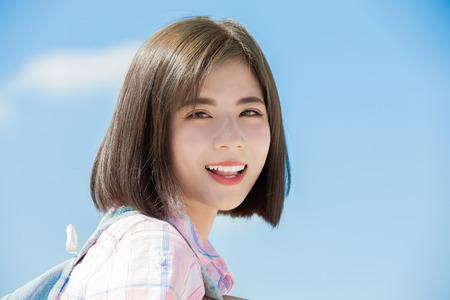 asiatischer student tavel und lächel dich mit himmelhintergrund an Standard-Bild