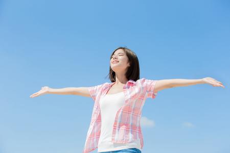 Asiatisches Mädchen fühlt sich glücklich und genießt die Natur mit Himmel