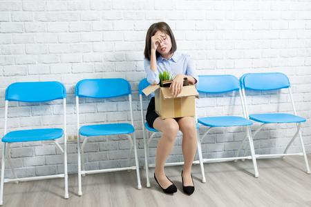 La empresaria asiática es despedida con la caja en la mano y se siente frustrada Foto de archivo