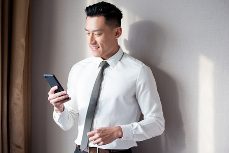 Asian businessman use cellphone and smile in the office Stock Photo