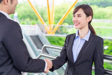 Businesspeople shake hand with confident smile after a meeting