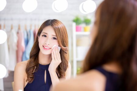 Close up of smile asian beauty woman moisturizing by cleansing cotton and look mirror
