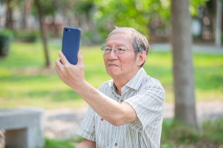 Older man selfie by cellphone in the park