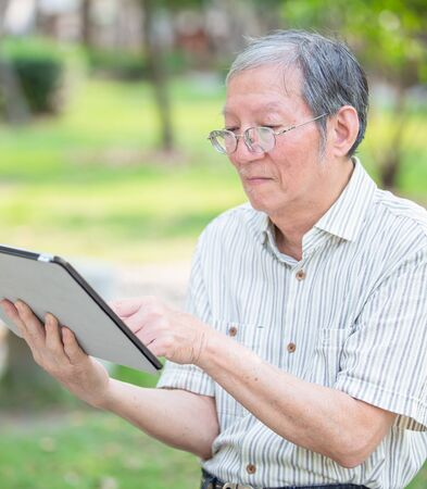 Older man use tablet in the park Stockfoto