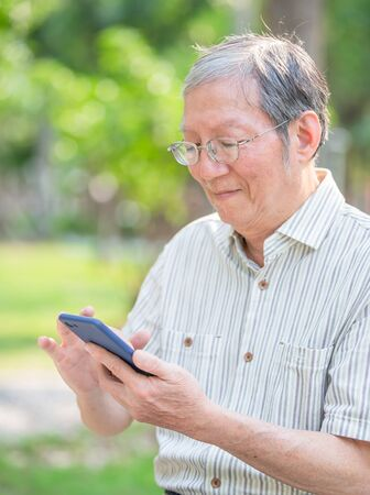 Older man use cellphone in the park