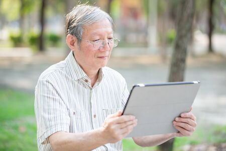 Older man use tablet in the park Stock Photo