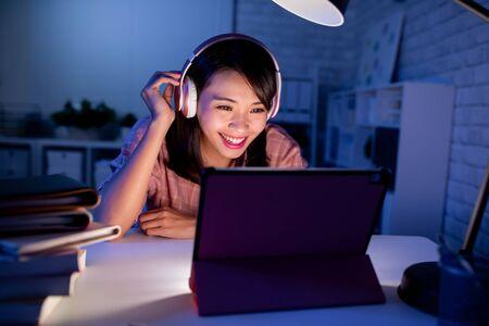 estudiante asiática usa la tableta digital por la noche