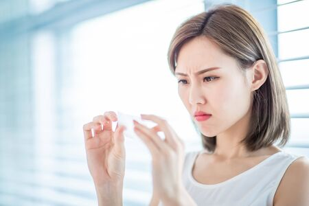 Young asian skin care woman upset after use oil blotting paper on her face