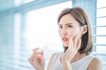 Young asian skin care woman upset after use oil blotting paper on her face Imagens
