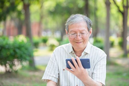 Older man watch video by cellphone in the park