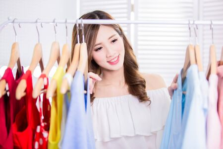 young woman choosing clothes on a rack in a showroom Stockfoto
