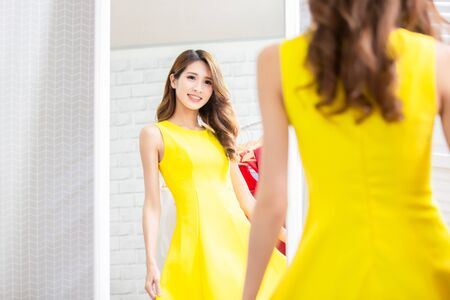 asian girl trying dress and looking in mirror cheerful