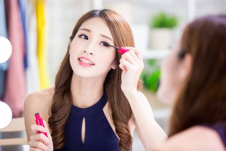beautiful woman using mascara brush and look mirror at home Stock fotó