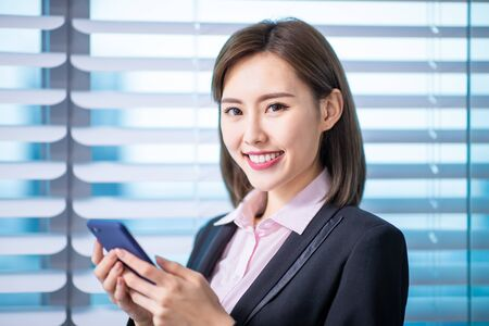 Young asian business woman use smart phone and smile to you in the office Stock fotó