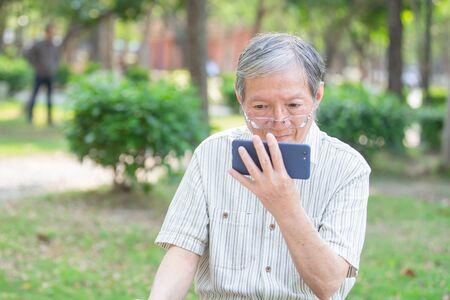 Älterer Mann nimmt die Brille ab und sieht sich Videos per Handy im Park an