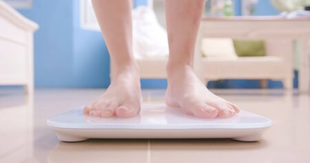 close up of woman stand on weight scale at home Banque d'images