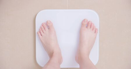 top view of woman stand on weight scale at home