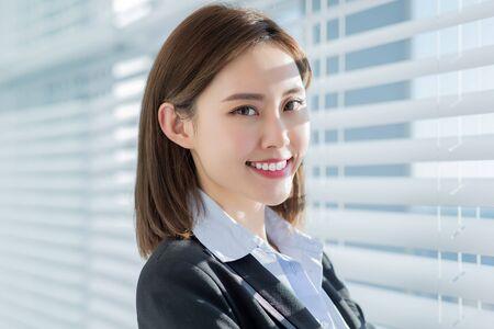 Aziatische zakenvrouw glimlacht vol vertrouwen naar je bij het gordijn op kantoor