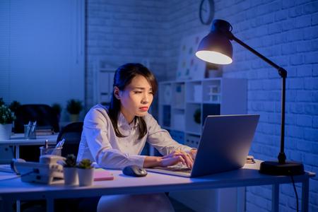 Asiatin macht Überstunden und fühlt sich im Büro müde Standard-Bild