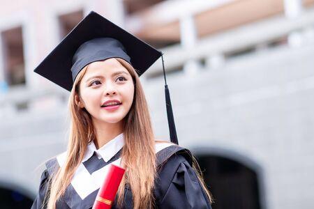 Niña gratuate sonrisa felizmente en el campus con diploma Foto de archivo