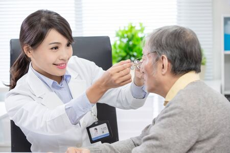 Female ophthalmologist see an elderly patient and helping him to wear glasses