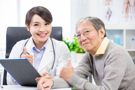 Vrouwelijke arts met oudere patiënt duimen opdagen Stockfoto