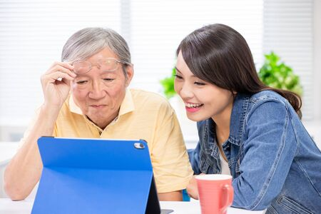 Young daughter teach elder father use tablet pc at home Stockfoto