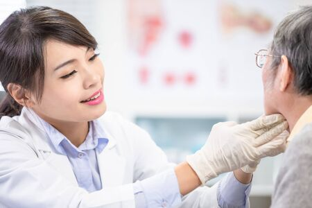 Female doctor check throat for elder patient carefully Stock Photo
