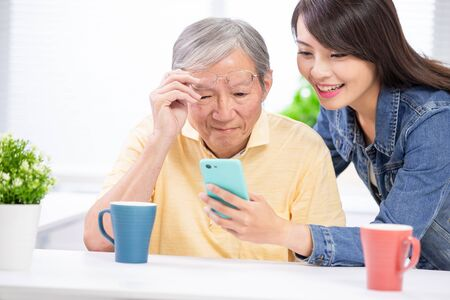 Young daughter teach elder father use mobile at home